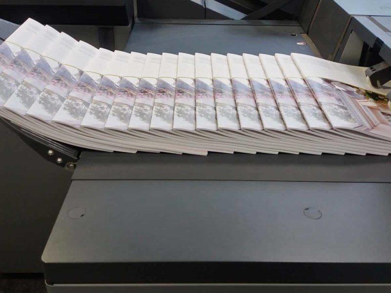 Dies ist einer unserer Broschürenfinisher. Hier werden die Broschüren an drei Seiten beschnitten und mit einem Buchrückenfalz oder auch Squarefold versehen. Der Rücken ist zweifach Drahtklammergeheftet.